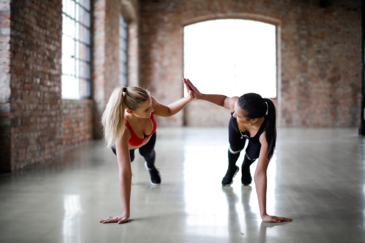"alt=""2 beautiful ladies working out, one as a health and fitness coach to assist the other in their fitness journey."""