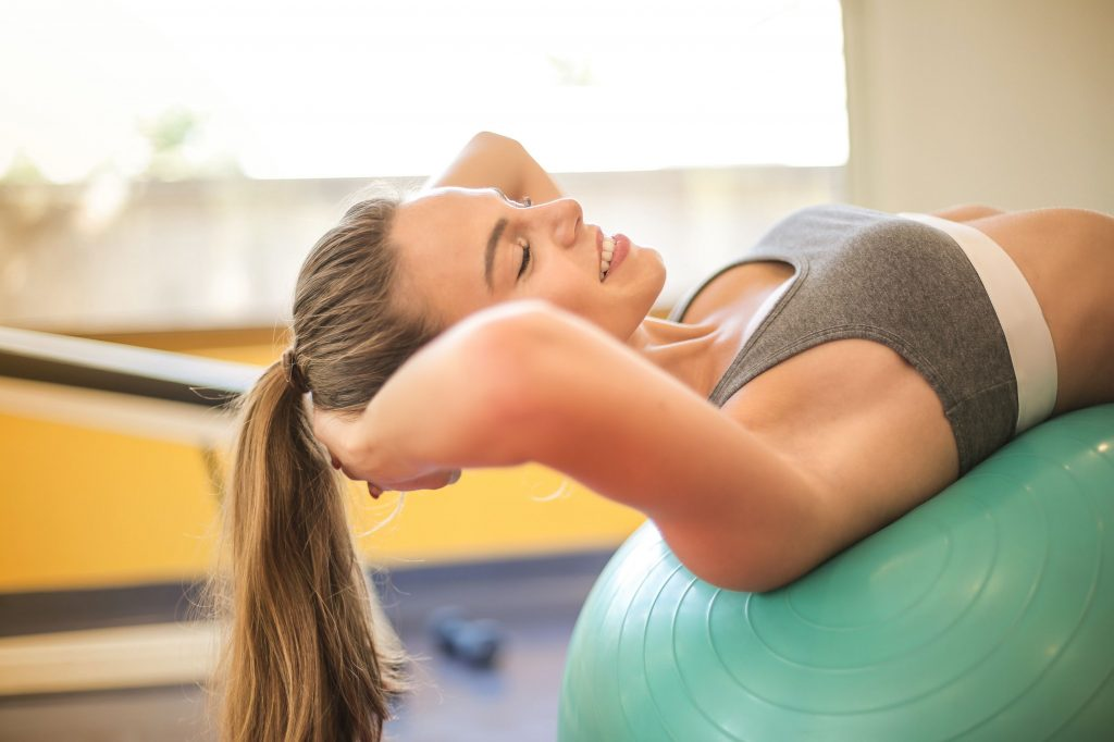 "alt=""A lovely lady smiling while exercise with a medicine ball to boost her mental fitness through bodybuilding."""