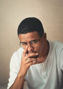 "alt=""A light skin man in glasses buried in thought with slight fear and anxiety."""