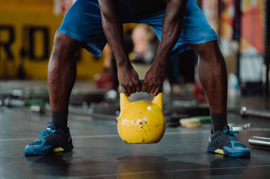 "alt=""Nice fit dark man carrying a yellow kettlebell boosting his fitness and strength."""