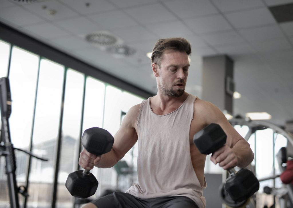 "alt=""good looking white male doing bodybuilding exercises to boost his health and fitness."""
